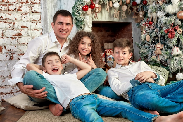 Kerst familie. geluk. portret van vader, moeder en kinderen van verschillende leeftijden zitten op de bank