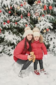 Kerst familie in winter park. gelukkige familiemoeder en kinddochter die pret hebben, die bij de wintergang in openlucht spelen. outdoor familieplezier op kerstvakantie. winterkleding voor baby en peuter.