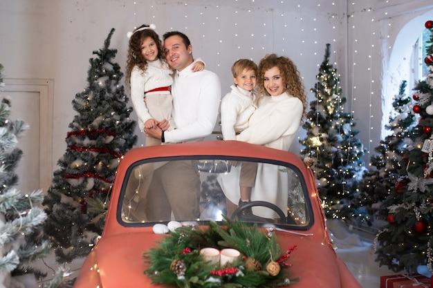 Kerst familie. moeder, vader en kleine kinderen in rode auto in de buurt van kerstbomen.