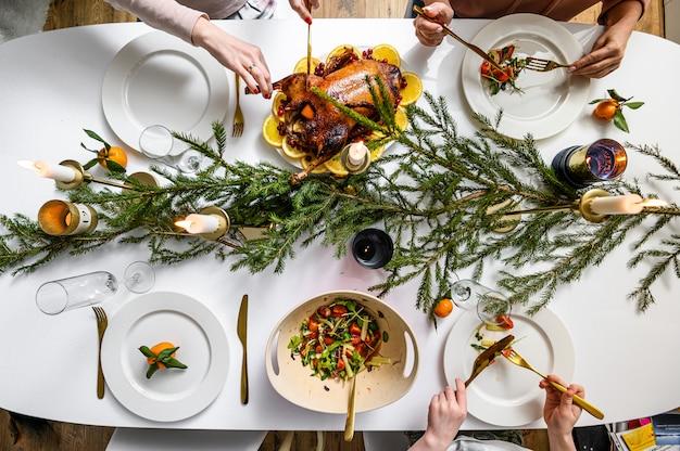Kerst feestelijk diner. heerlijke traditionele vakantiemaaltijd en handen van mensen die hen eten. versierde tafel met smakelijke gerechten. flat ley. witte tafel