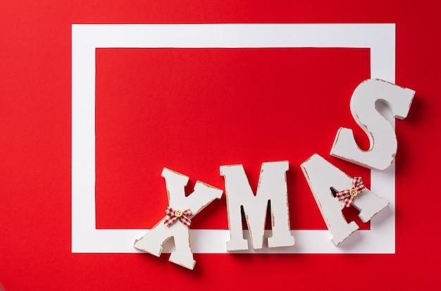 Kerst feestelijke achtergrond. wit frame met rode kerstversiering op rode achtergrond. plaats voor tekst. bovenaanzicht.