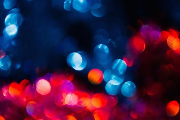 Kerst feestelijke bokeh achtergrond wazig. regen op het raam. kleurrijk abstract stadslichtenconcept