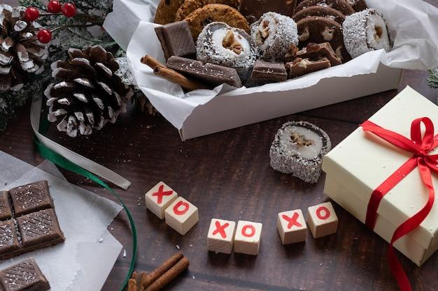 Kerst feestelijke geschenkdoos en snoep met seizoensversieringen op houten achtergrond