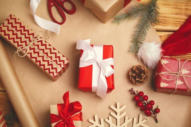 Kerst feestelijke stemming. plat van decoraties, linten, cadeaupapier, ingepakt cadeau op houten achtergrond