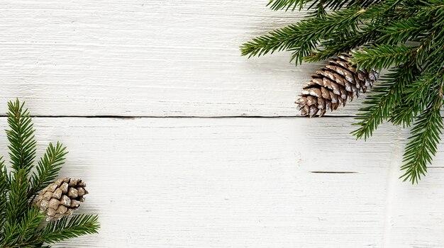 Kerst fir boomtakken en dennenappels op oude witte houten achtergrond.