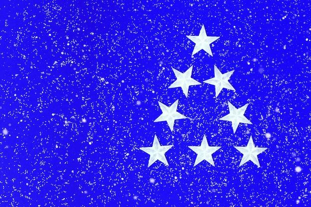 Kerst fon met witte sterren in vorm driehoek kerstboom op blauwe wintervakantie concept