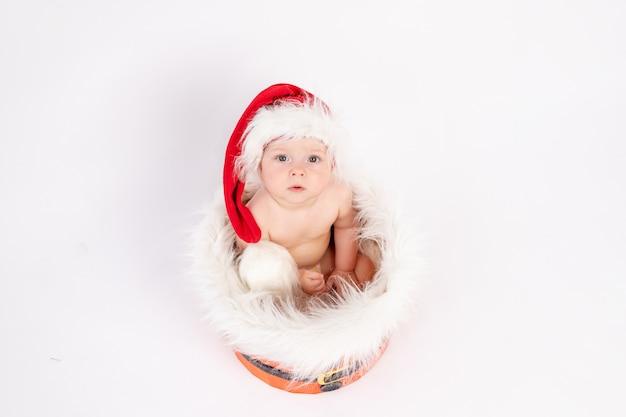 Kerst foto een klein kind meisje zit in een kerstmuts in een mand in de buurt van de kerstbomen op wit