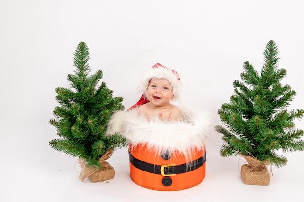 Kerst foto een klein kind meisje zit in een kerstmuts in een mandje in de buurt van de kerstbomen