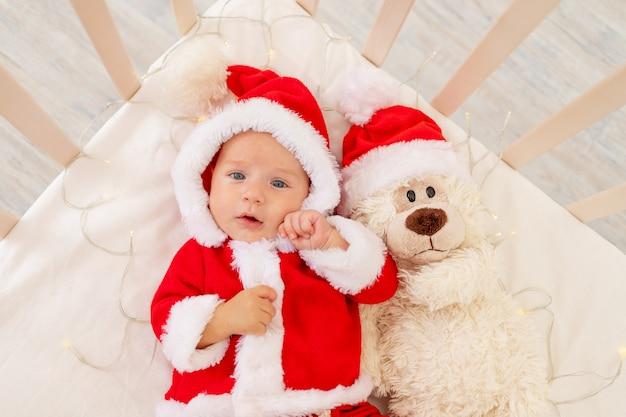 Kerst foto van een baby in een kerstman kostuum liggend in een wieg thuis met een speeltje in een kerstman hoed