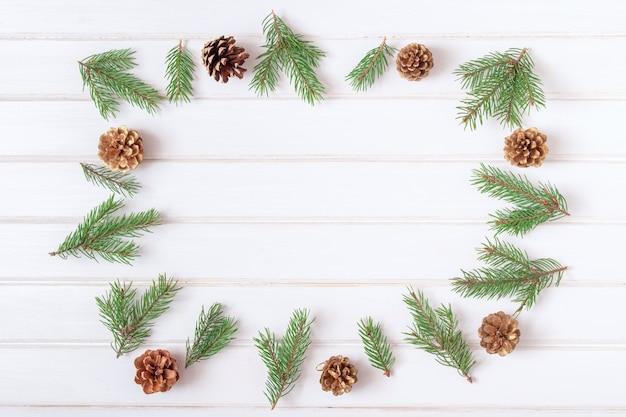 Kerst frame en achtergrond concept. bovenaanzicht van vuren takken en dennenappels aangelegd in de vorm van een cirkel op vintage oude witte houten achtergrond. ruimte kopiëren.