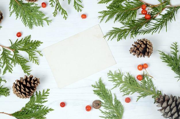 Kerst frame. fir tree takken en rowan bessen op een witte achtergrond. bovenaanzicht compositie