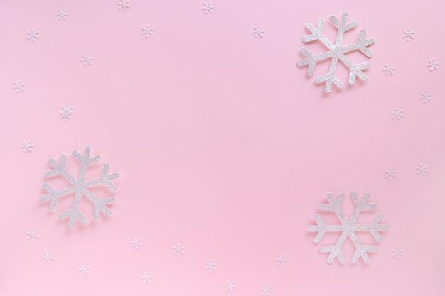 Kerst frame gemaakt van sneeuwvlokken op pastelroze