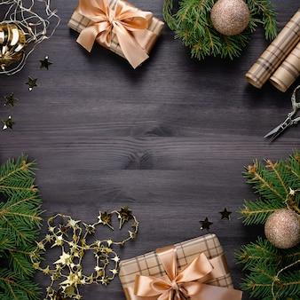 Kerst frame met dennen, cadeautjes, gouden kerstballen op zwart