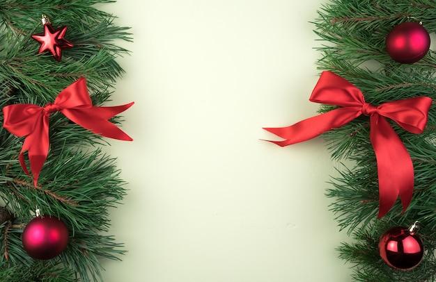 Kerst frame met pijnboomtakken versierd met rood speelgoed en strikken