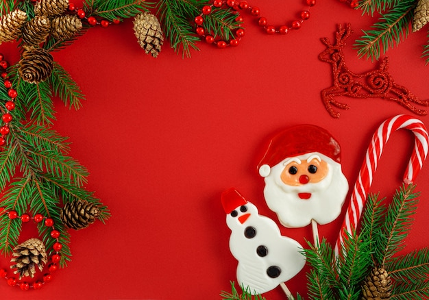 Kerst frame met traditionele snoepjes, bont en kegels op rood