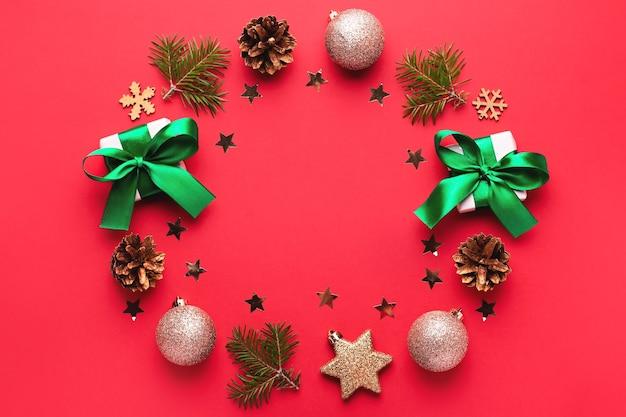 Kerst frame op rode achtergrond met pijnboomtakken, kegels, geschenken, decoraties en confetti. feestelijke, kleurrijke kerstachtergrond met rode en groene elementen, kopieerruimte, bovenaanzicht