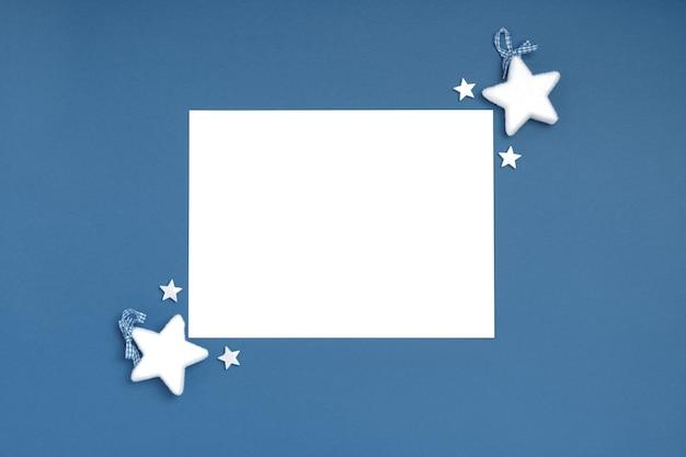 Kerst frame samenstelling. blanco vel papier met kerstversiering op blauwe achtergrond. Premium Foto