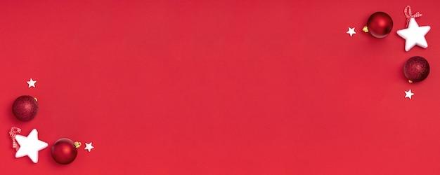 Kerst frame samenstelling. blanco vel papier met kerstversiering op rode achtergrond.