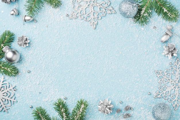 Kerst frame van decoraties, sparren en zilveren new year's ornamenten op blauwe tafel.