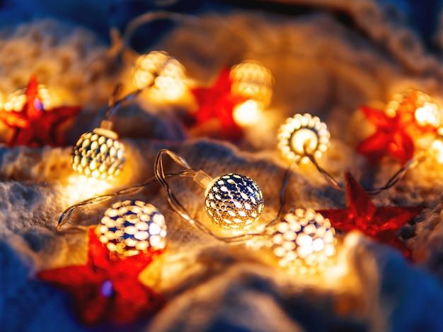 Kerst gebreide gloeilampen en rode sterren. gezellige vakantiedecoratie.