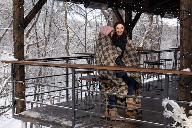 Kerst gelukkige paar verliefd omarmen in besneeuwde winter koude bos