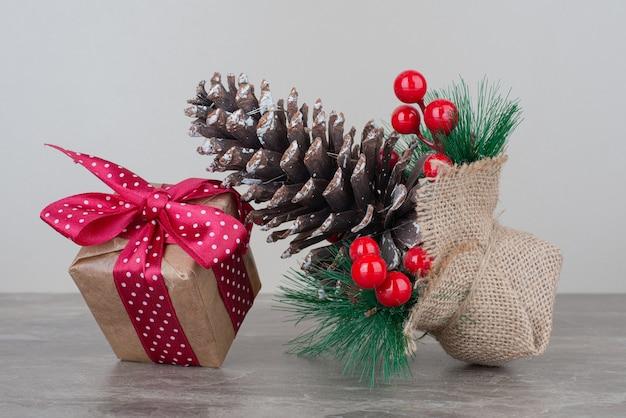 Kerst geschenkdoos en pinecone op marmeren tafel.