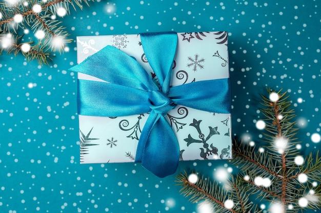 Kerst geschenkdoos met diy boog en dennentakken met getrokken sneeuw op turkoois.