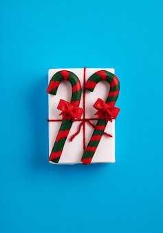 Kerst geschenkdoos met een rood lint versierd met zuurstokken