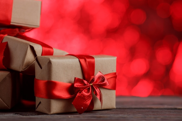 Kerst geschenkdoos met lint op houten tafel tegen abstracte rode achtergrond.