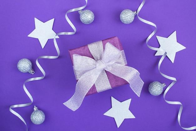 Kerst geschenkdoos met zilveren strik op de paarse achtergrond. bovenaanzicht. detailopname.