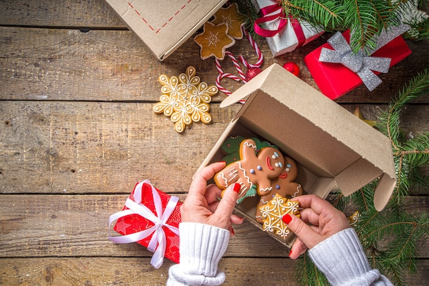 Kerst geschenkdoos pakket. cadeau uitwisseling kerst nieuwjaar concept op covid-19 pandemie. secret santa post-spel. geschenken inpakken, koekjes in pakket. houten achtergrond, met kerstboomtak en decor