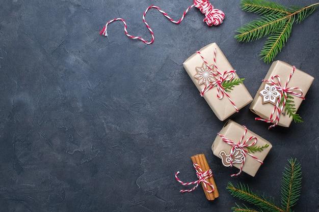 Kerst geschenkdozen en decoraties, pijnboomtakken op donkere tafel. plat leggen