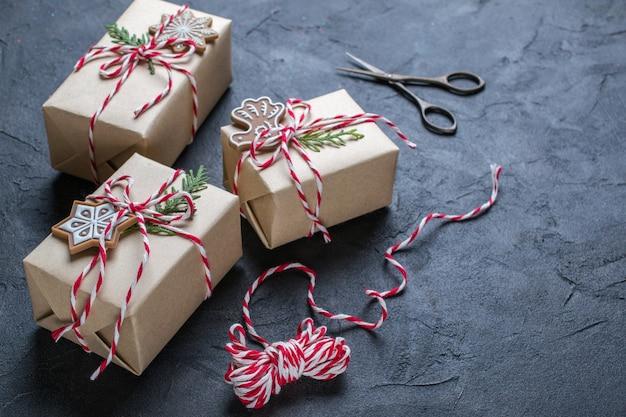 Kerst geschenkdozen en decoraties, pijnboomtakken op donkere tafel.