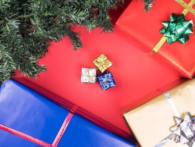 Kerst geschenkdozen en kerstboom op rode achtergrond. traditie sieraad.