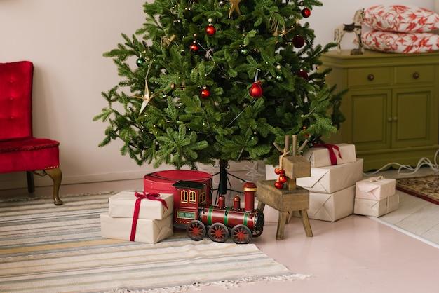 Kerst geschenkdozen en speelgoed onder de kerstboom met verlichting
