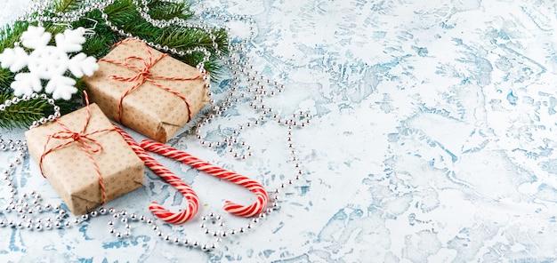 Kerst geschenkdozen, fir tak met kegels, zuurstokken op licht