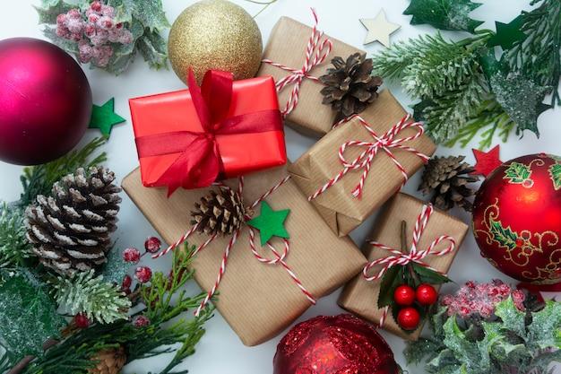 Kerst geschenkdozen, gestileerde fir takken, dennenappels, witte achtergrond.
