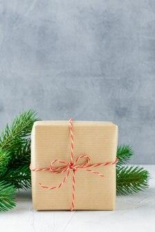 Kerst geschenkdozen in kraftpapier en vuren takken op grijs beton