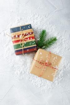 Kerst geschenkdozen in kraftpapier en vuren takken op sneeuw. bovenaanzicht