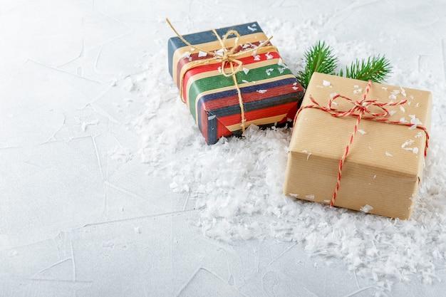 Kerst geschenkdozen in kraftpapier en vuren takken op sneeuw