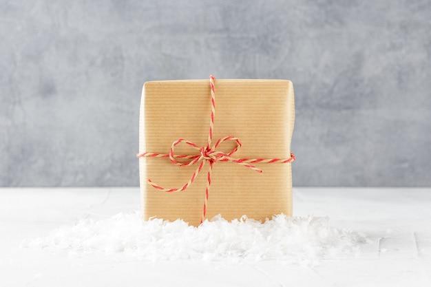 Kerst geschenkdozen in kraftpapier op sneeuw