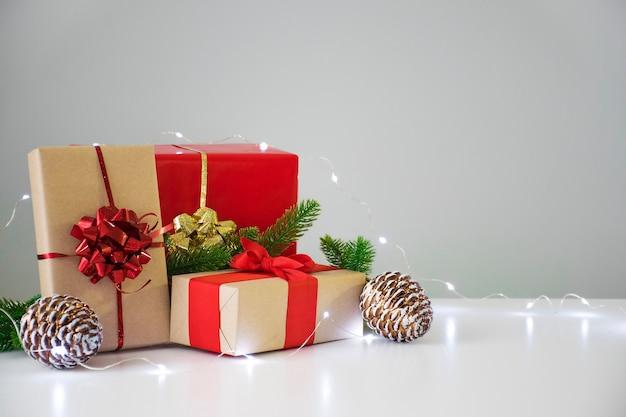 Kerst geschenkdozen in rood en ambachtelijk bruin met dennentakken, dennenappels en lichten op grijs