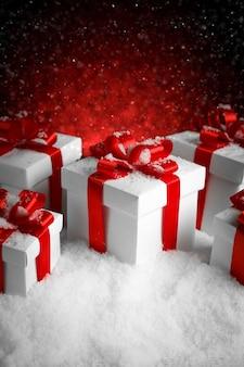 Kerst geschenkdozen met een grote rode strik die zich in verse sneeuw bevindt