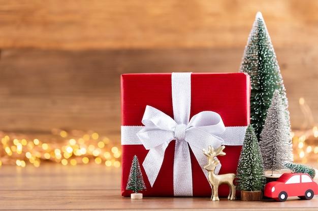 Kerst geschenkdozen met linten en boom op bokeh achtergrond.