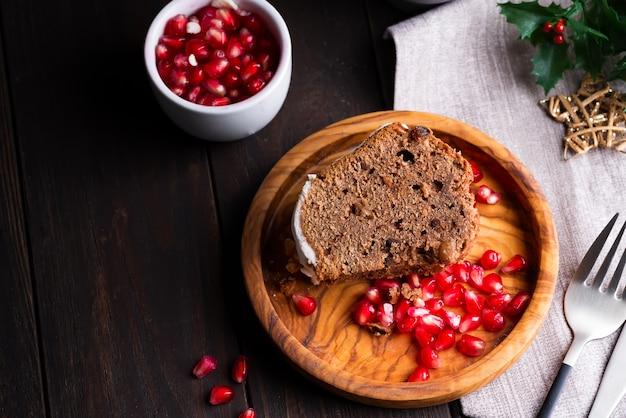 Kerst gesneden chocoladetaart met witte suikerglazuur en granaatappel kernels een houten donker, plat lag
