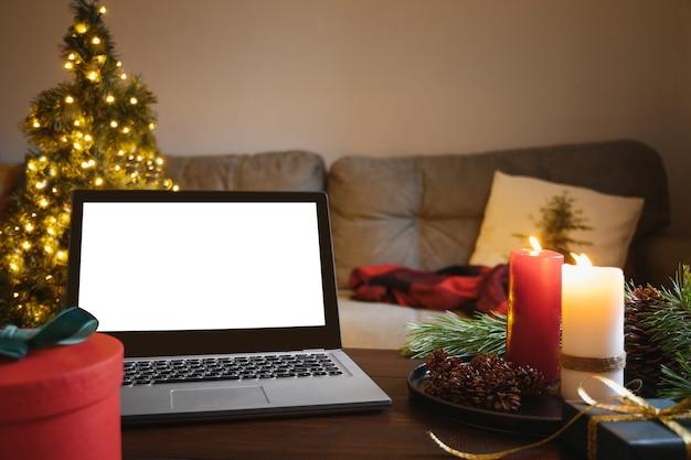 Kerst gezellig interieur in woonkamer met laptop en kaarsen om naar de bioscoop te kijken. kerst thuis.