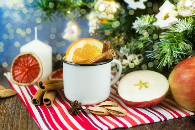 Kerst glühwein frisdrank warme compote in metalen mok met gedroogde vruchten kaneel sinaasappels
