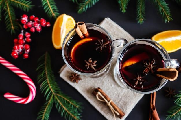 Kerst glühwein in glazen met kaneel en sinaasappelen op feestelijke kerst