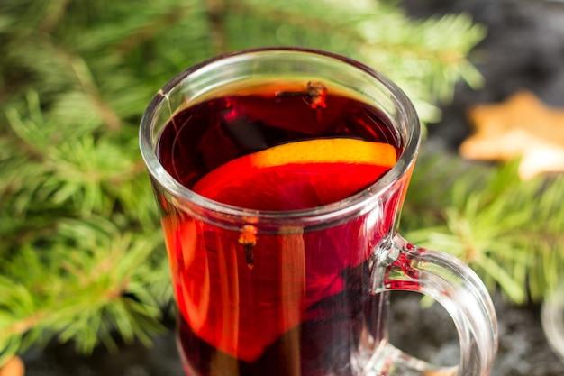 Kerst glühwein met gemberkoekjes oranje kaneel kruidnagel anijs en dennenboom op de donkere zwarte tafel