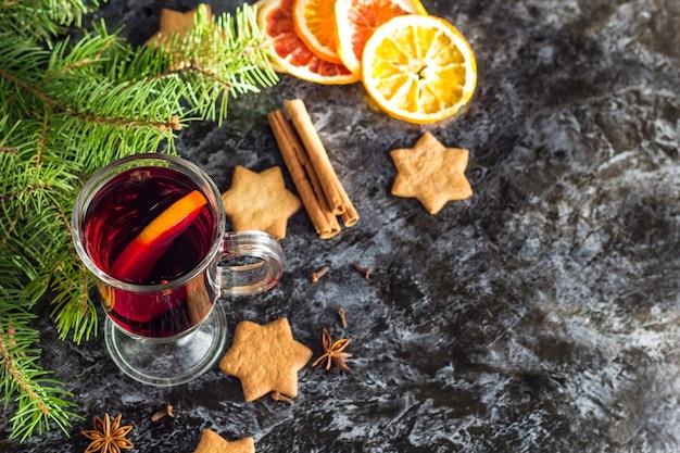 Kerst glühwein met gemberkoekjes sinaasappel kaneel kruidnagel anijs en dennenboom op de donkere zwarte tafel